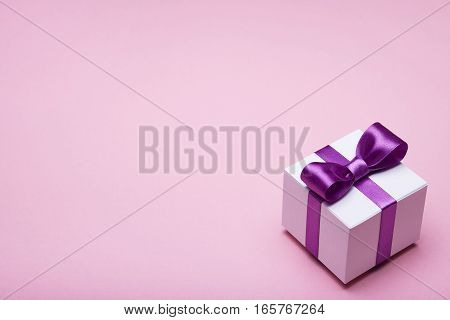 Gift in a beautiful package, bow from satin ribbon, box with gifts, attributes festive mood, gift on a pink background