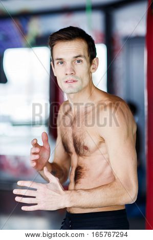 Portrait of young sportsman without shirt in gym