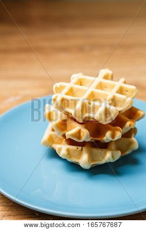 Three fresh homemade waffles on blue plate