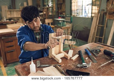 Professional Vietnamese carpenter chiseling wooden chair leg