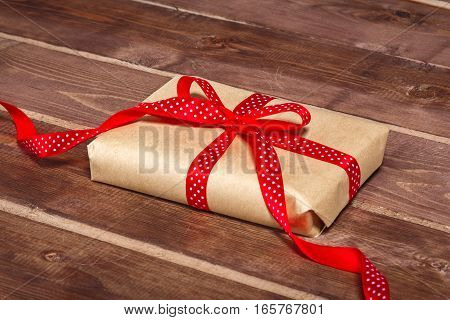 Wrapped vintage gift box with red ribbon bow on wooden background can use on valentine day mother day or celebrate love day .