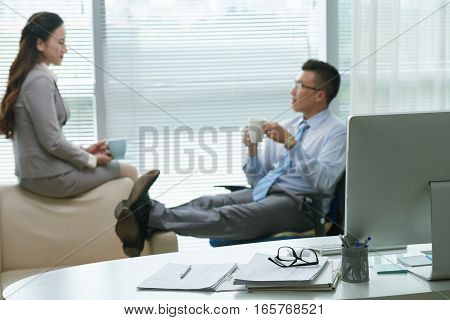 Coworkers drinking coffee and chatting during the break