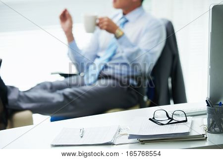 Glasses and documents on table of businessman