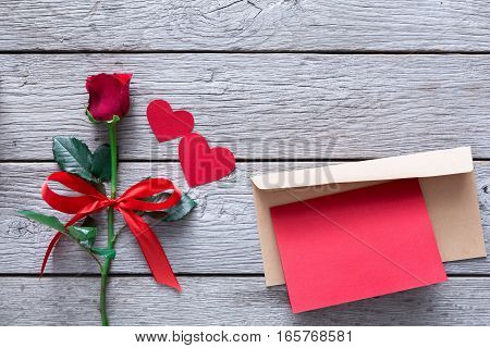 Valentine background with red rose flower and handmade paper hearts and greeting card in envelope on rustic wood. Happy lovers day confession letter mockup, copy space