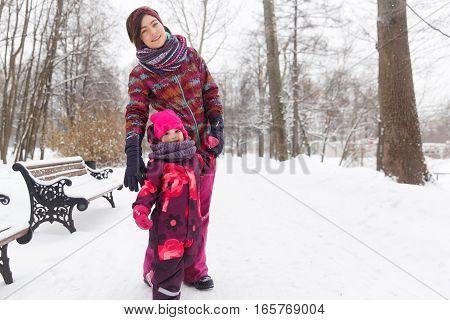 Happy family on walk in winter woods