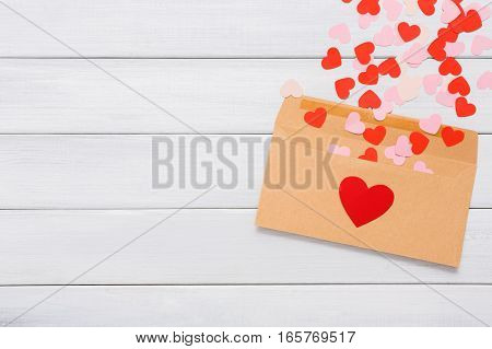 Valentine day love letter. Envelope from craft paper with red hearts heap spread on white wood background. Lover's holiday confession or proposal concept