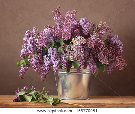 Bouquet of purple lilac in a bucket. Still life in rustic style.