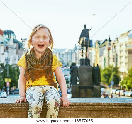 The spirit of old Europe in Prague. Portrait of smiling modern child on Wenceslas Square in Prague Czech Republic sitting on the parapet