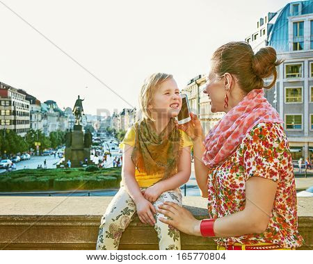 Mother And Daughter Travellers In Prague Using Smartphone