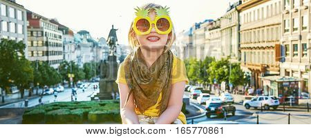 The spirit of old Europe in Prague. Portrait of happy modern child on Wenceslas Square in Prague Czech Republic in pineapple sunglasses sitting on the parapet