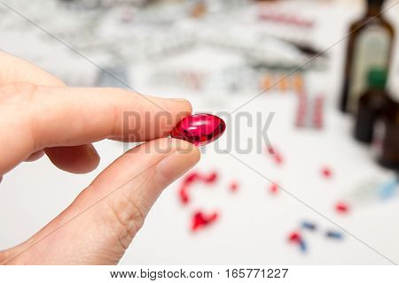 Red capsule with vitamins in fingers. Hand holding pills. Helthcare concept