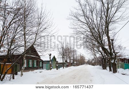 Rostov Veliky / Russia - DECEMBER 22: Old wooden houses and trees on Pushkinskaya Street on December 22 2016 in Rostov Veliky. Rostov Veliky is town in Yaroslavl Oblast Russia.