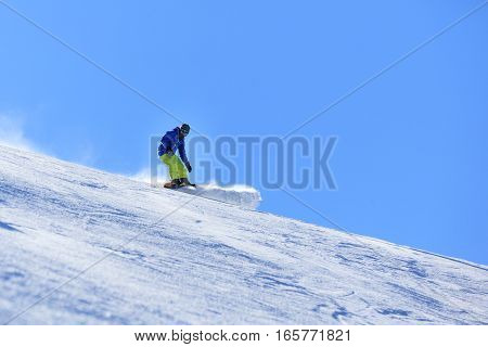 Male snowboarder on the slope sliding down the hill