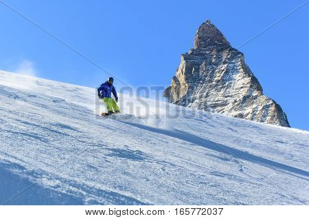Male snowboarder on the slope with Matterhorn mountain peak on background