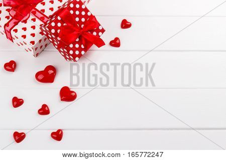 Red hearts and gift boxes on white wooden board, Valentine day card template