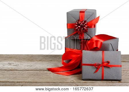 Group of gift boxes wrapped with paper and red satin ribbon on wood isolated on white background. Modern presents for any holiday, christmas, valentine or birthday