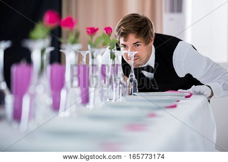 Handsome Waiter Looking At Wedding Table Arrangement At Restaurant poster