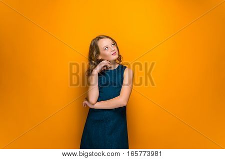 The happy teen girl with long hair looking up on orange studio background