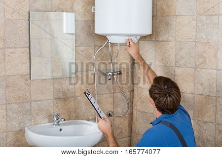 Young Male Plumber Holding Clipboard Checking Electric Boiler In Bathroom