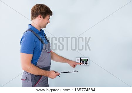 Side View Of Man Setting Security System And Holding Clipboard At Home
