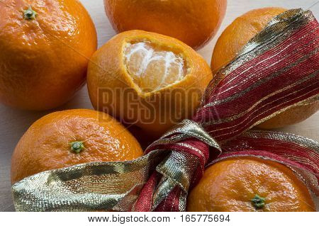 One mandarin with peel in heart form with red-yellow ribbon and several mandarins