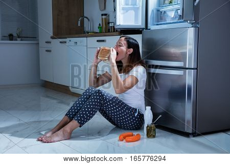 Young Woman Eating Sandwich With Jar Of Pickle While Sitting On Floor In Kitchen