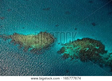 Aerial view to coral reefs in ocean. Maldivian islands