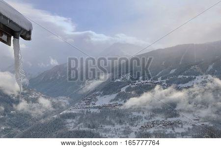 village in mountain under clouds and stalactite on a roof