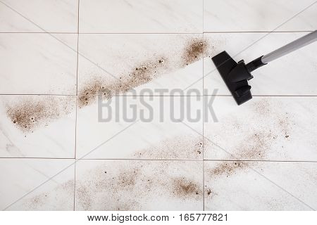 Close-up Of Person Vacuuming The Dust Of The Floor At Home