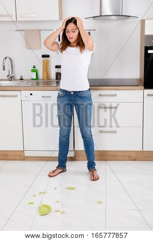 Frustrated Young Woman Looking At Broken Plate Fallen On The Floor In The Kitchen