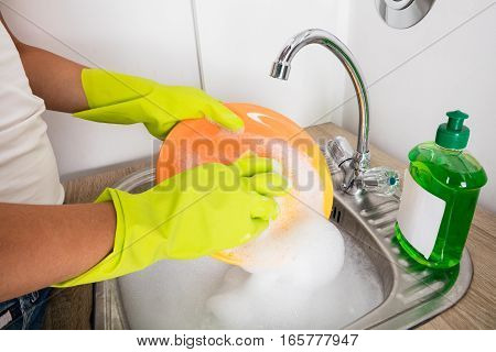 Close-up Of Person Washing Plate On Soapy Water In The Kitchen