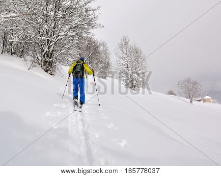 man climbing mountain with ski touring in the snow