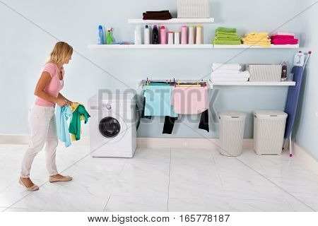 Happy Woman Walking With Stained Clothes To Washing Machine In Utility Room
