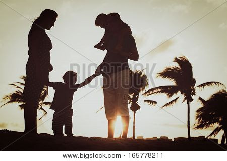 silhouette of happy family with two kids at sunset beach