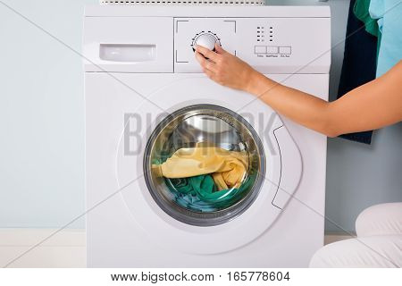 Close-up Of Person Hand Pressing Button Of Washing Machine For Clothes Laundry