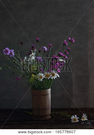 Still life with blue wild flowers and daisies in vase