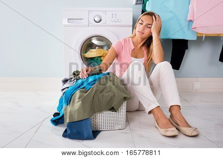 Young Unhappy Woman Looking At Pile Of Dirty Clothes Near Washing Machine At Utility Room
