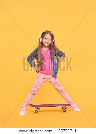 Pretty little girl standing on yellow background. Vertical full length portrait of Kid girl wearing headphones and colorful pink trendy clothes
