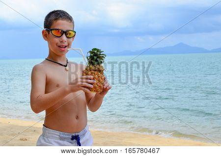 Boy Enjoying A Pineapple Drink On Beautiful Tropical Beach
