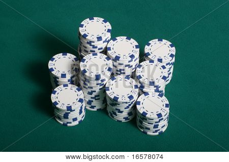 Poker chips stacked up on a green felt poker table