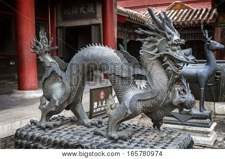 China Beijing . Summer emperor Palace . Figures of mythical creatures at the entrances to the building. Bronze figures of a dragon and the deer - symbols of longevity and fertility .