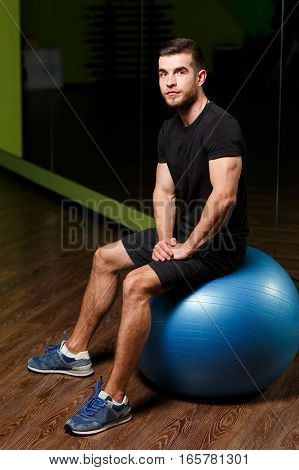 Young sportsman sits on fitball at sports center