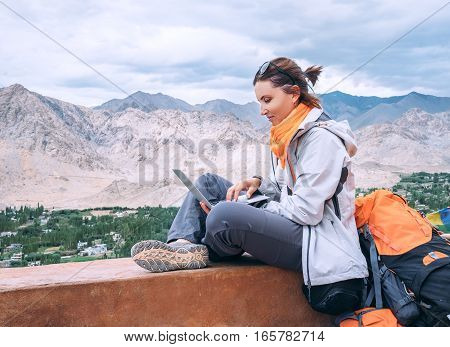 Backpacker with laptop sits on the top view point under mountain settelment