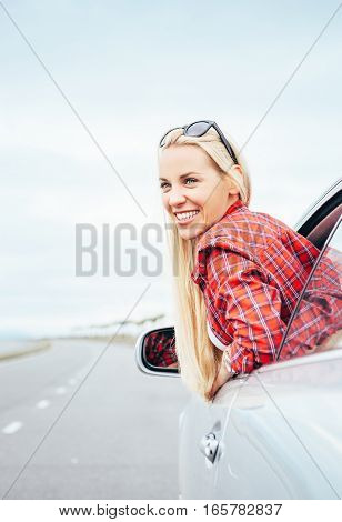 Happy smiling young woman looks out from car window