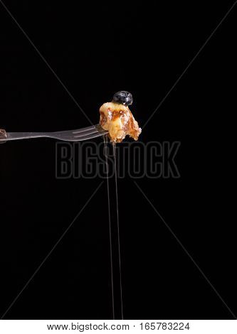 Blueberry waffle set in a nice dish and a fork cut in piece with pouring honey on black background copy space.