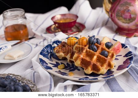 Blueberry apple waffle with honey set on a dish decorated with fresh blueberry, apple and almond.