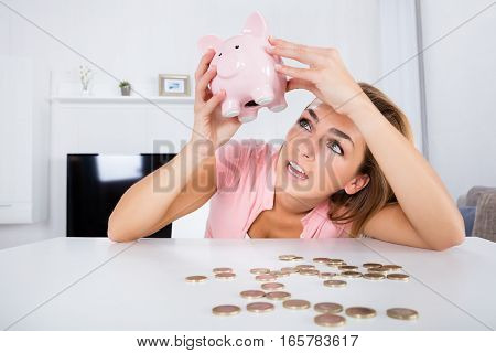 Young Unhappy Woman Emptying Her Piggybank Savings With Less Than Expected At Home