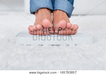Close-up Of Person Feet Standing On Weighing Scale Showing Help Text At Home