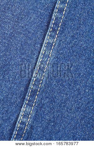 Texture of deep blue jeans fabric with diagonal yellow double stitching