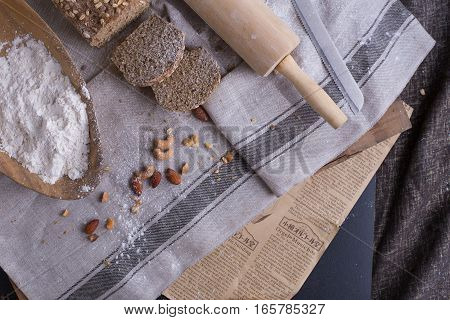Cut whole grain wheat bread in pieces set on nice fabric brown background decorated with flour bowl and a bakery wooden roller.